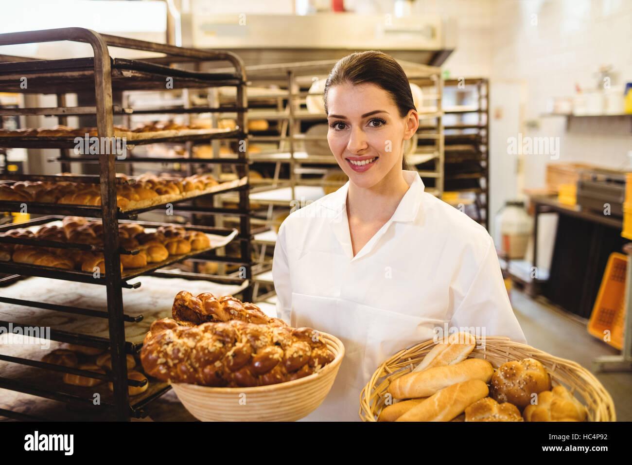 Female baker holding basket of sweet foods Stock Photo