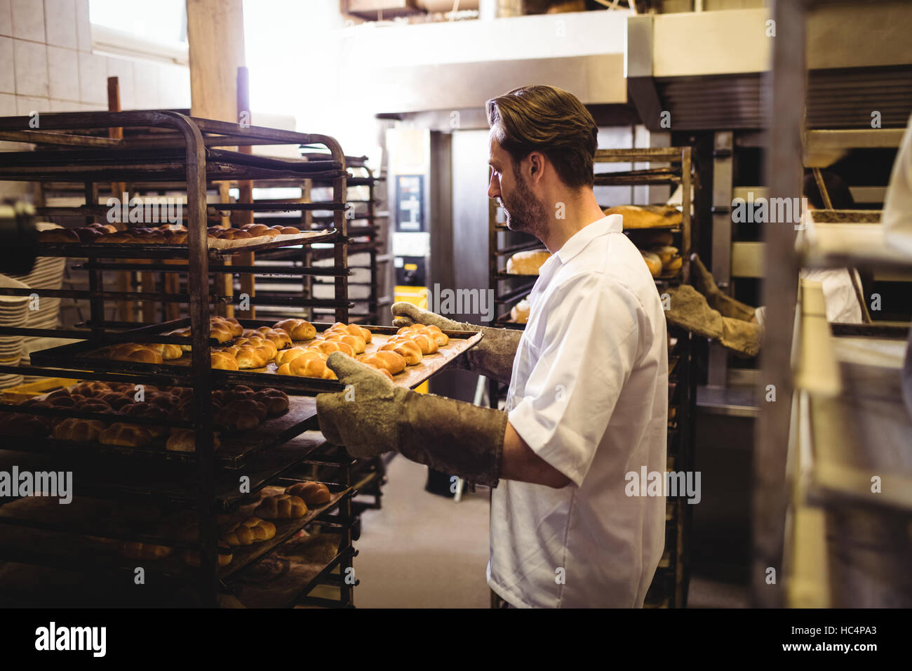 Male baker holding a tray of michetta - Stock Image