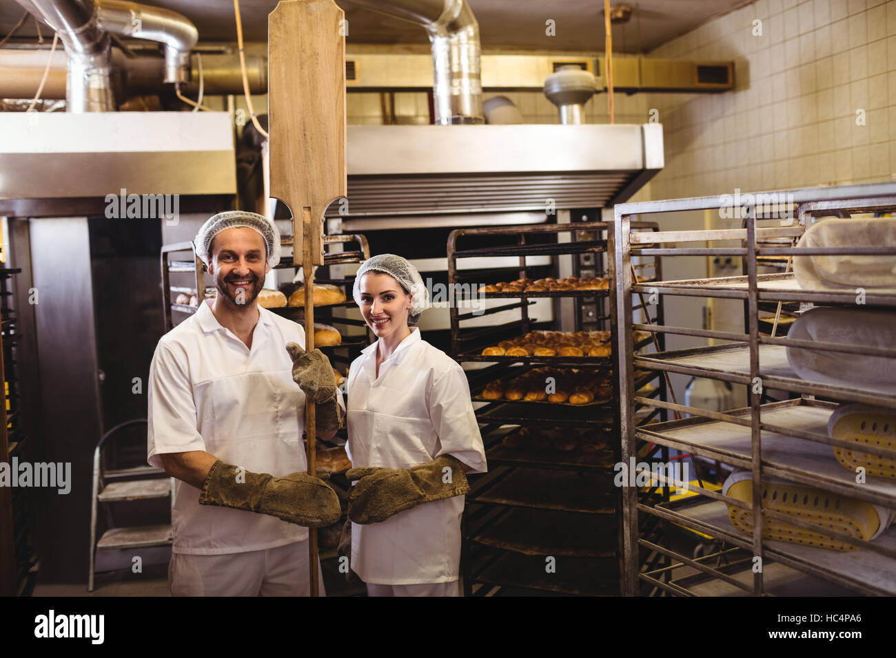 Portrait of female and male baker standing together - Stock Image