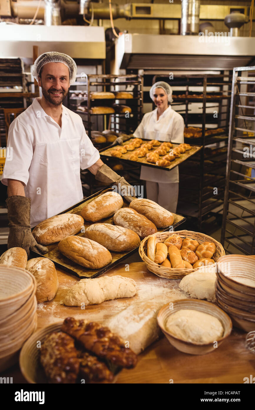 Male and female baker holding tray of loaf and michetta - Stock Image
