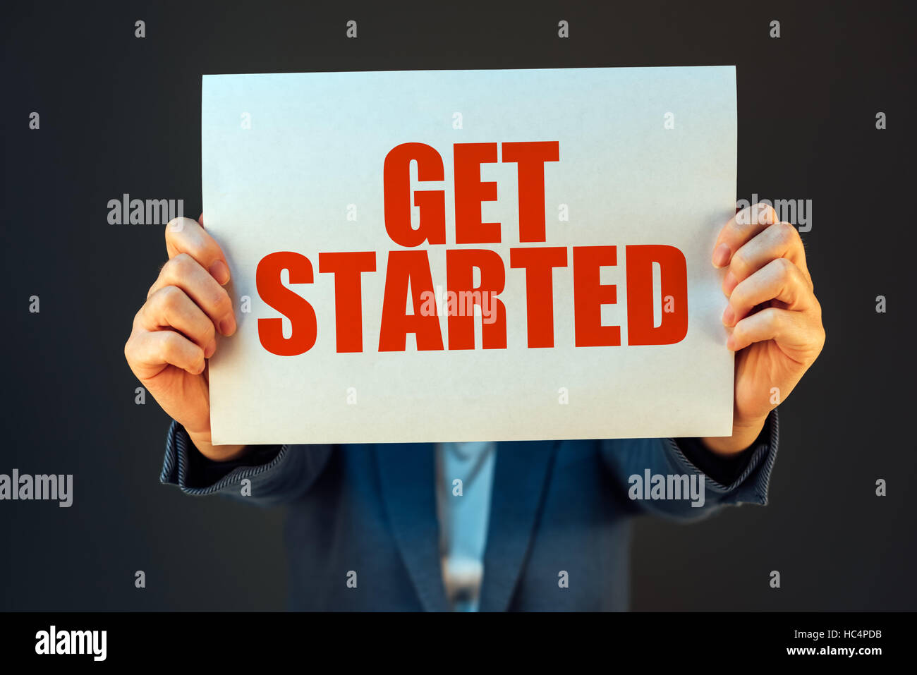 Get started business motivational message held by businesswoman, company start up concept - Stock Image