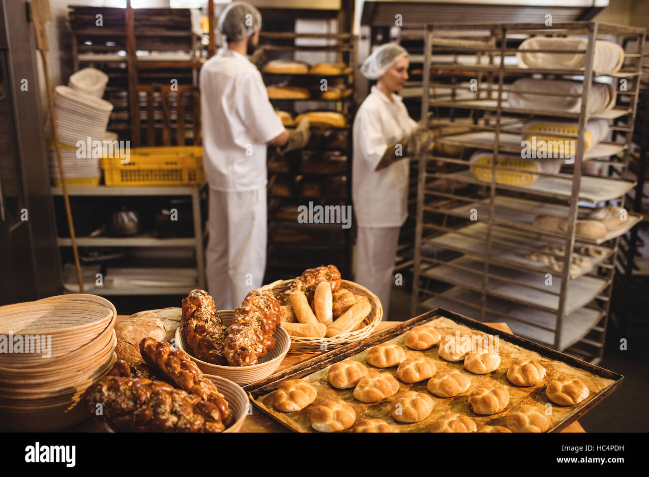 Michetta and sweet food on a table while male and female baker working in background - Stock Image