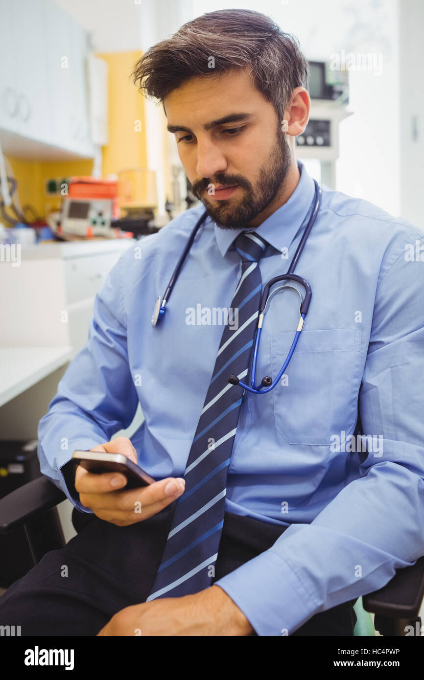 Doctor text messaging on mobile phone - Stock Image