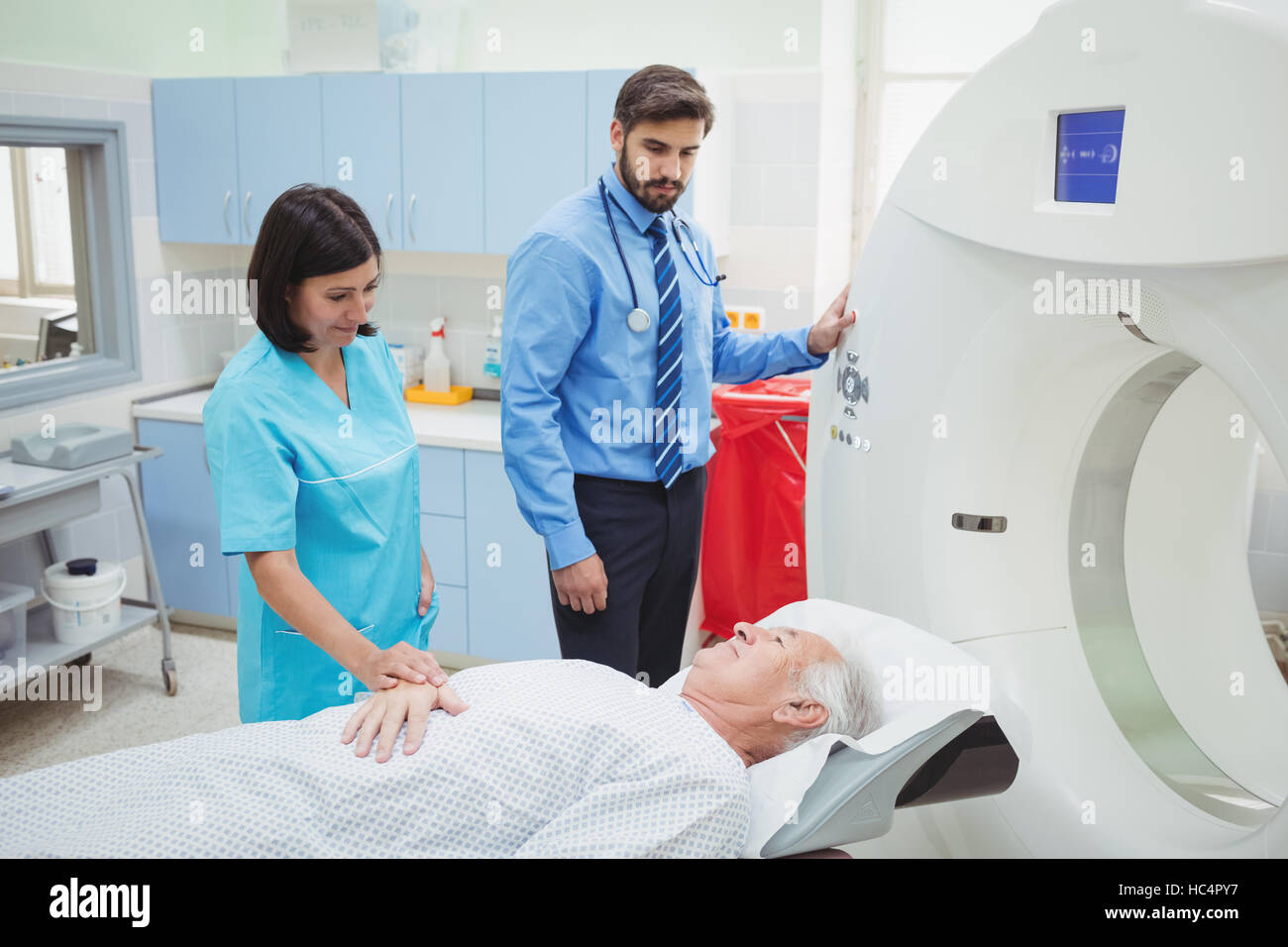 A patient is loaded into an mri machine while doctor and technician watching - Stock Image
