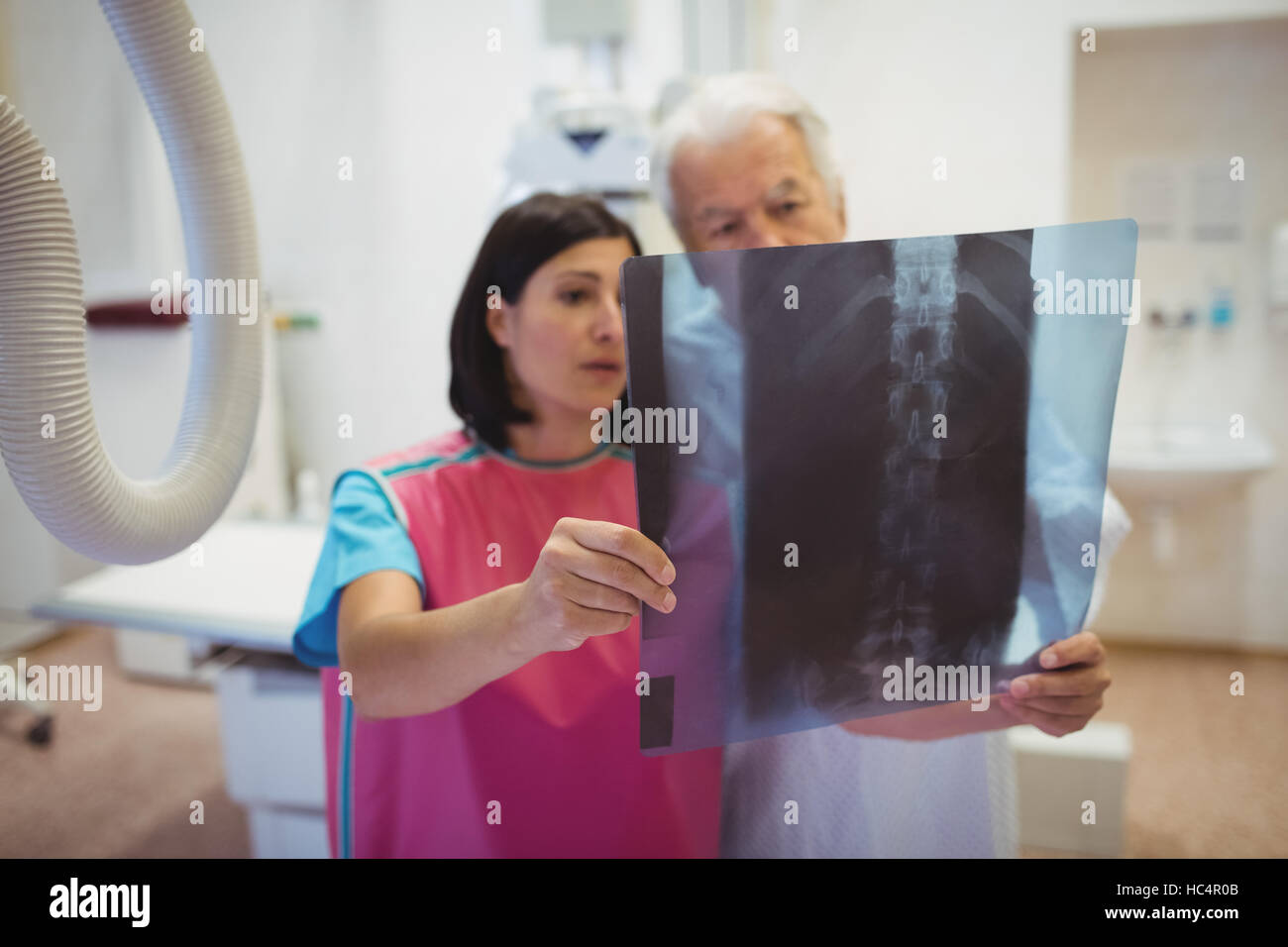 Female doctor discussing x-ray with patient - Stock Image