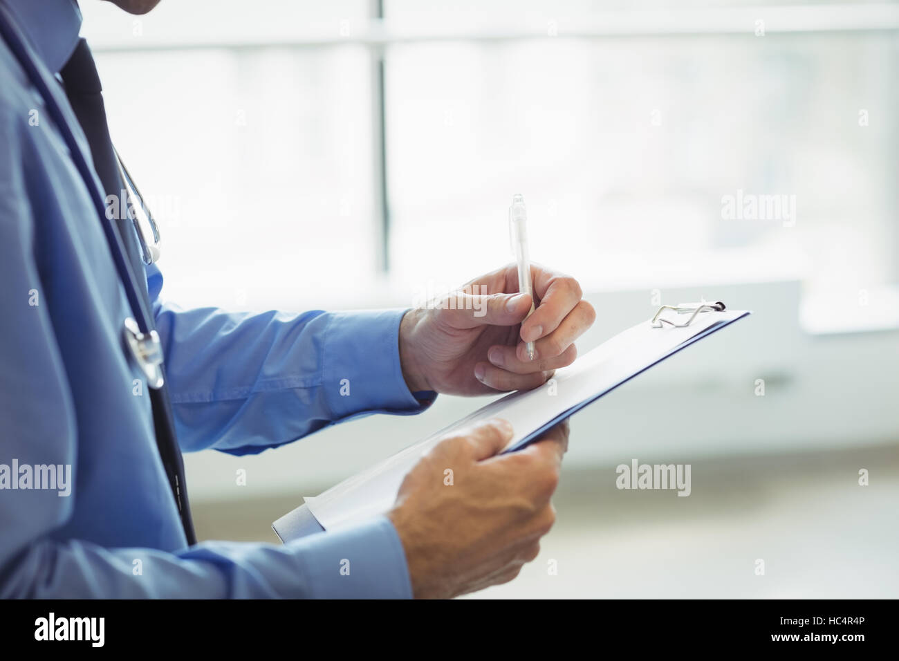 Mid section of doctor writing on clipboard - Stock Image