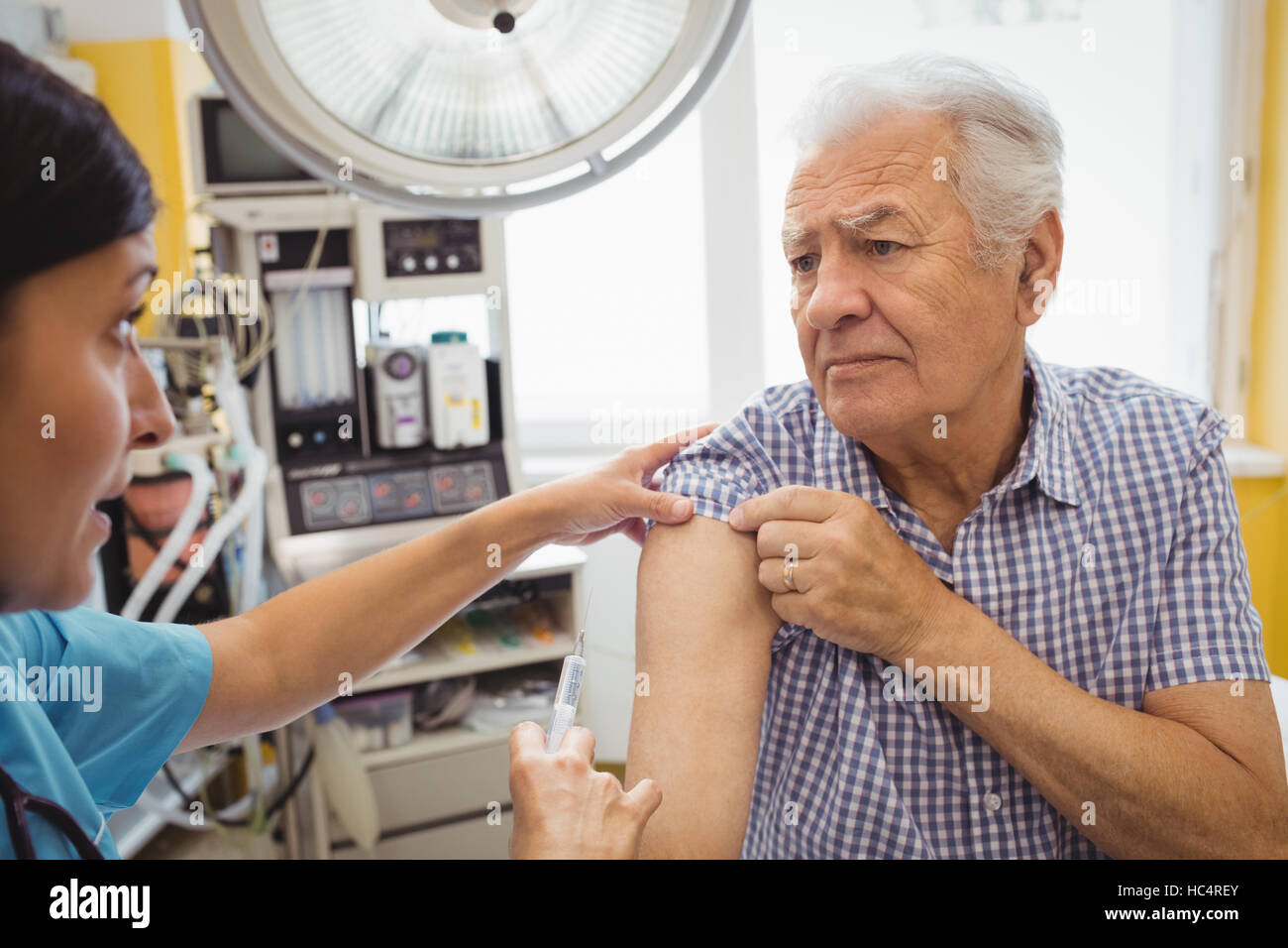 Female doctor giving an injection to a patient Stock Photo