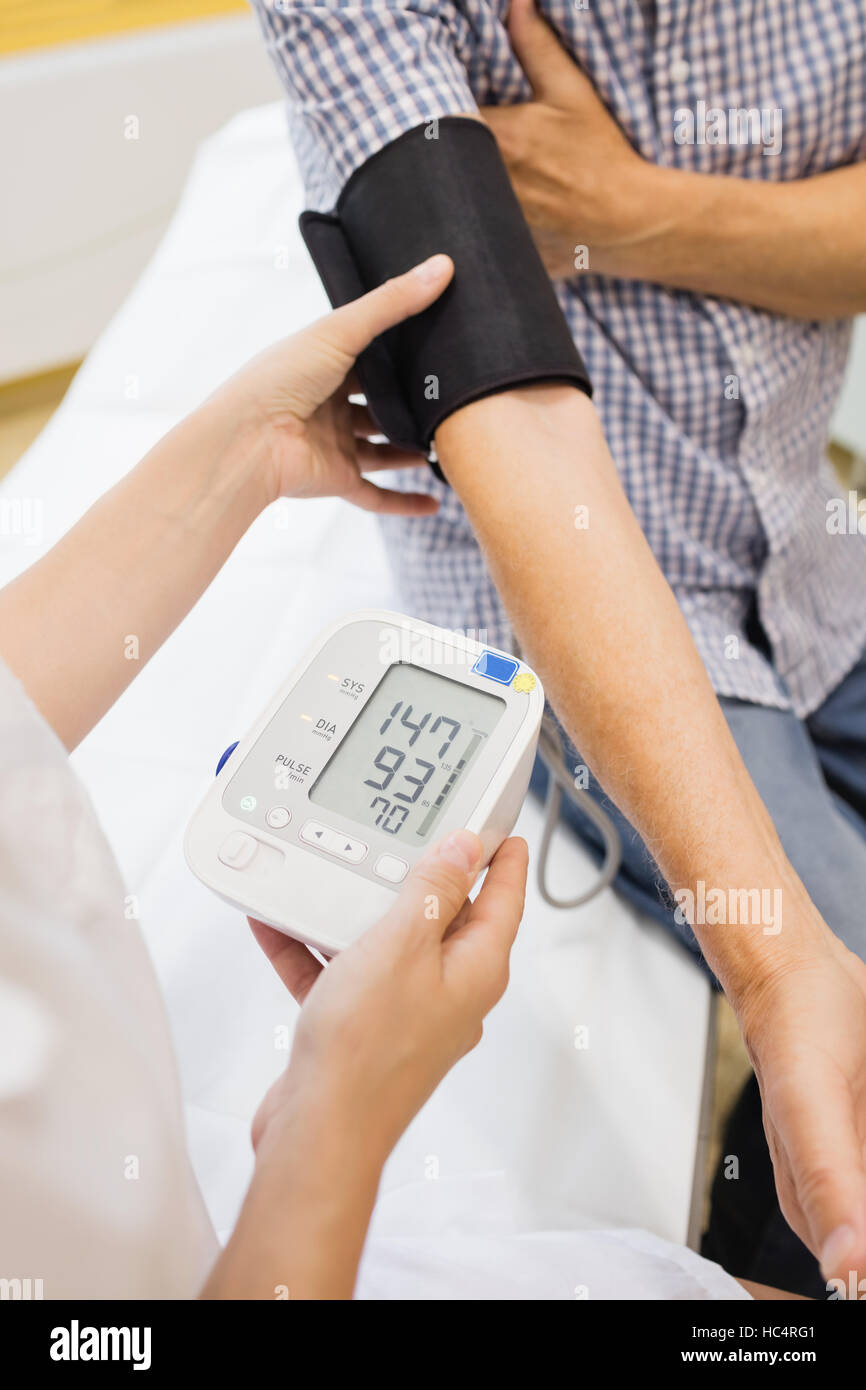 Female doctor checking blood pressure of patient - Stock Image
