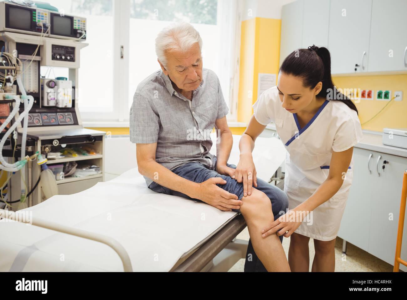 Female doctor examining patients knee - Stock Image