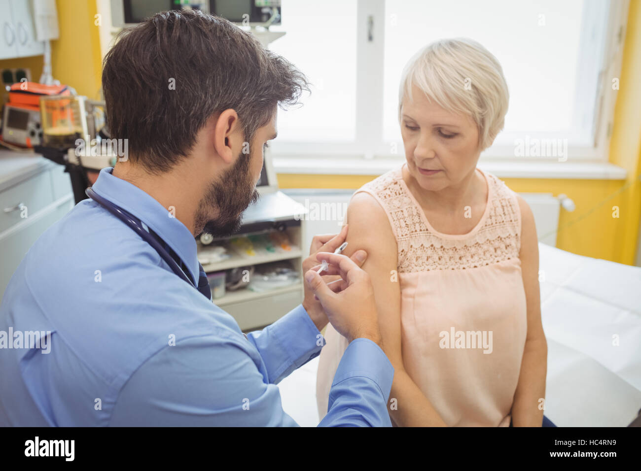 Male doctor giving an injection to a patient Stock Photo