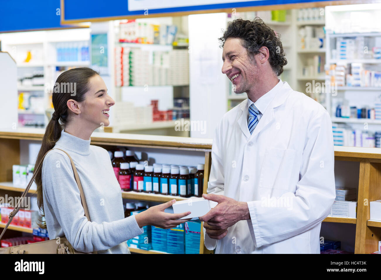 Pharmacist assisting the pills to customer - Stock Image