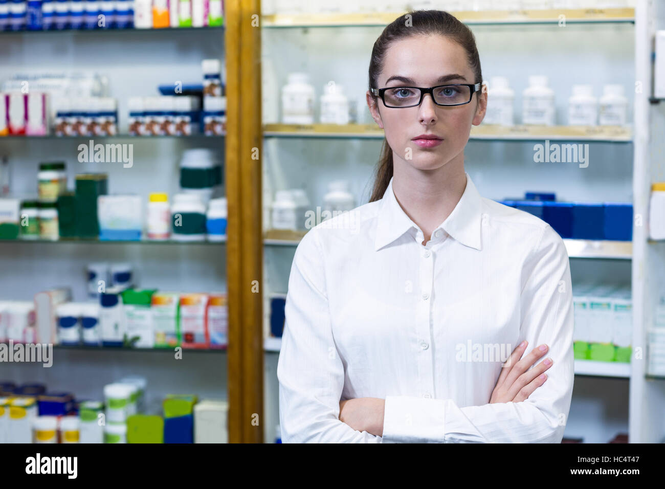 Pharmacist standing with arms crossed in pharmacy - Stock Image