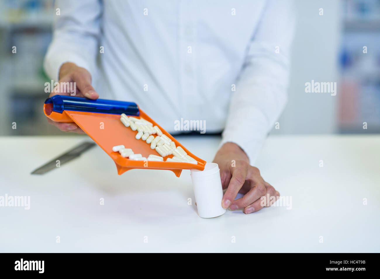 Pharmacist putting pill in container at pharmacy - Stock Image