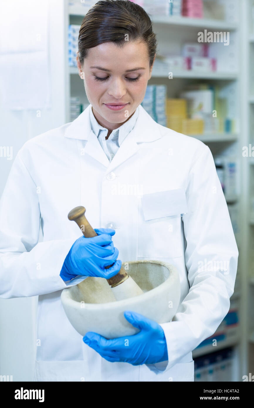 Pharmacist grinding medicine in mortal and pestle - Stock Image