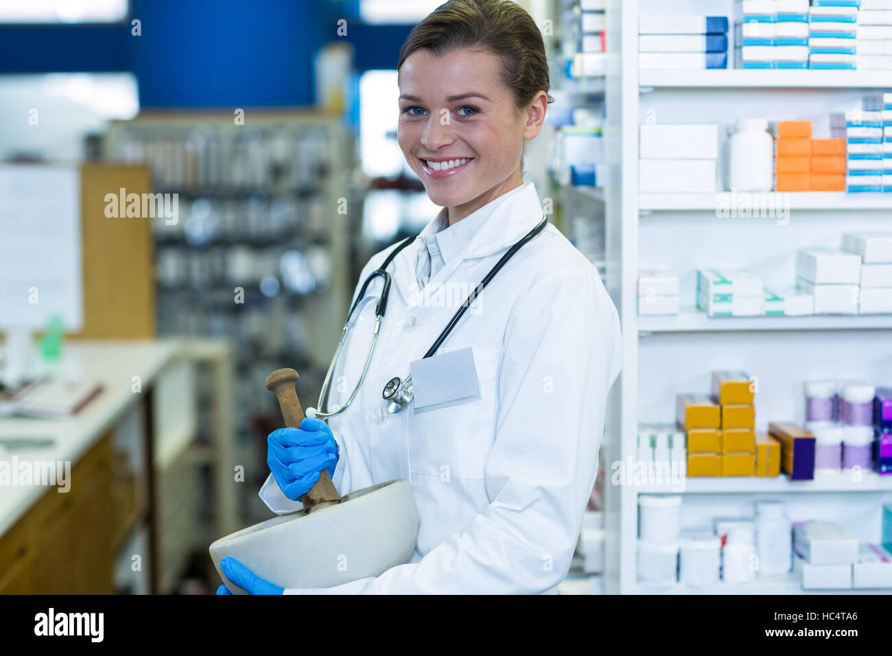 Pharmacist grinding medicine in mortal and pestle at pharmacy - Stock Image