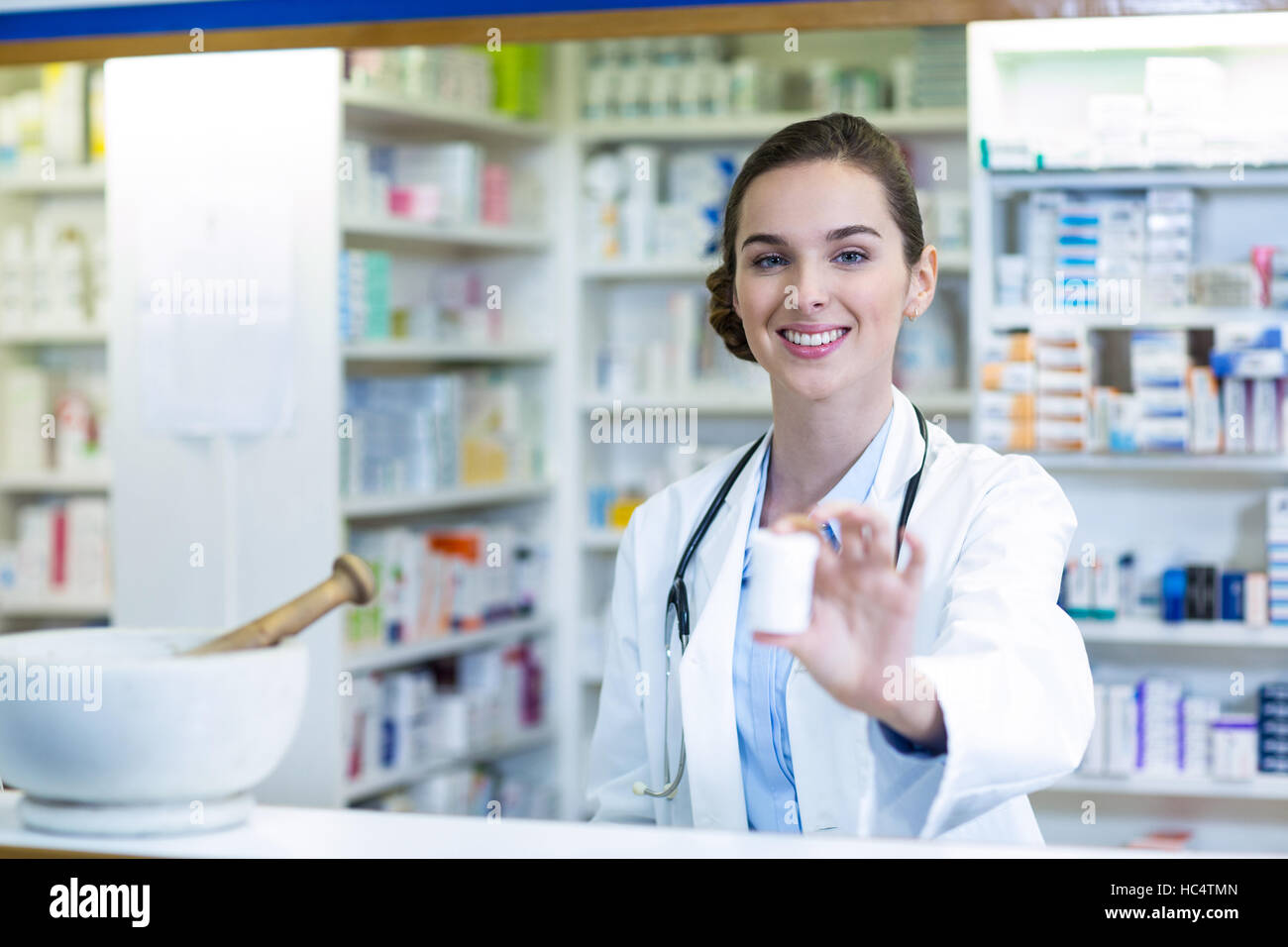Smiling pharmacist showing medicine container in pharmacy - Stock Image