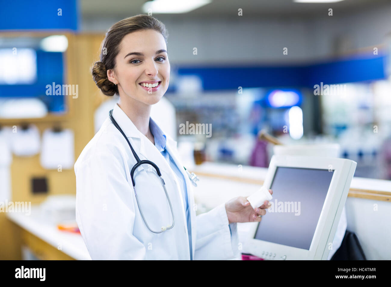Smiling pharmacist holding medicine container in pharmacy - Stock Image