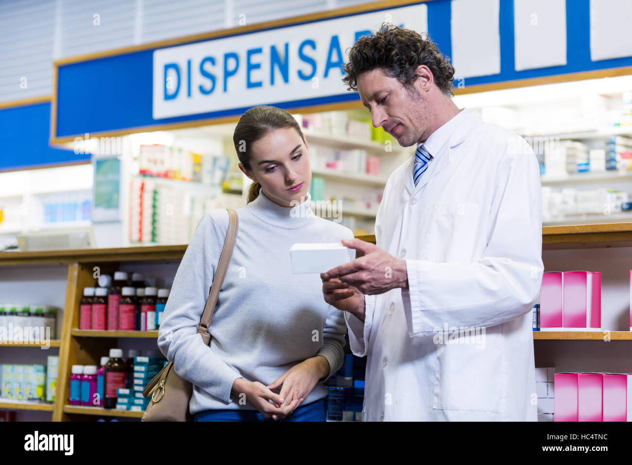 Pharmacist assisting the medicine to customer - Stock Image
