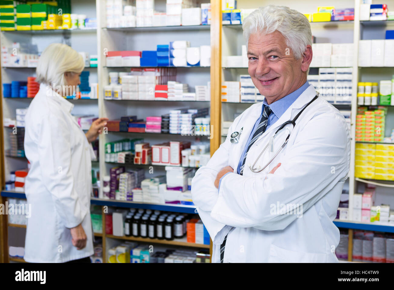 Pharmacist standing with arms crossed and co-worker checking medicines - Stock Image