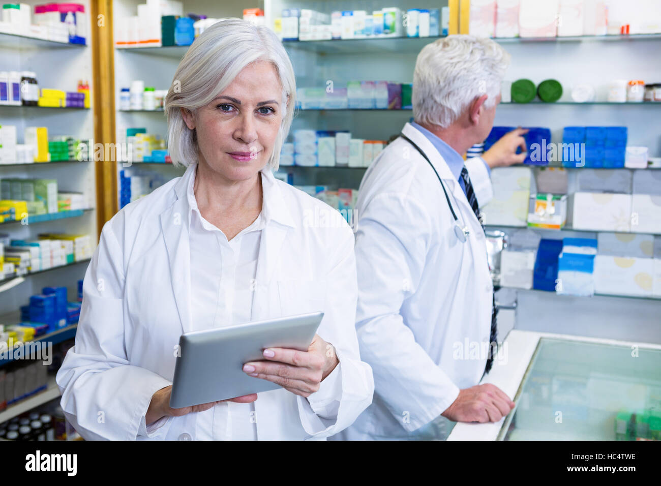 Pharmacist using digital tablet and co-worker checking medicines - Stock Image