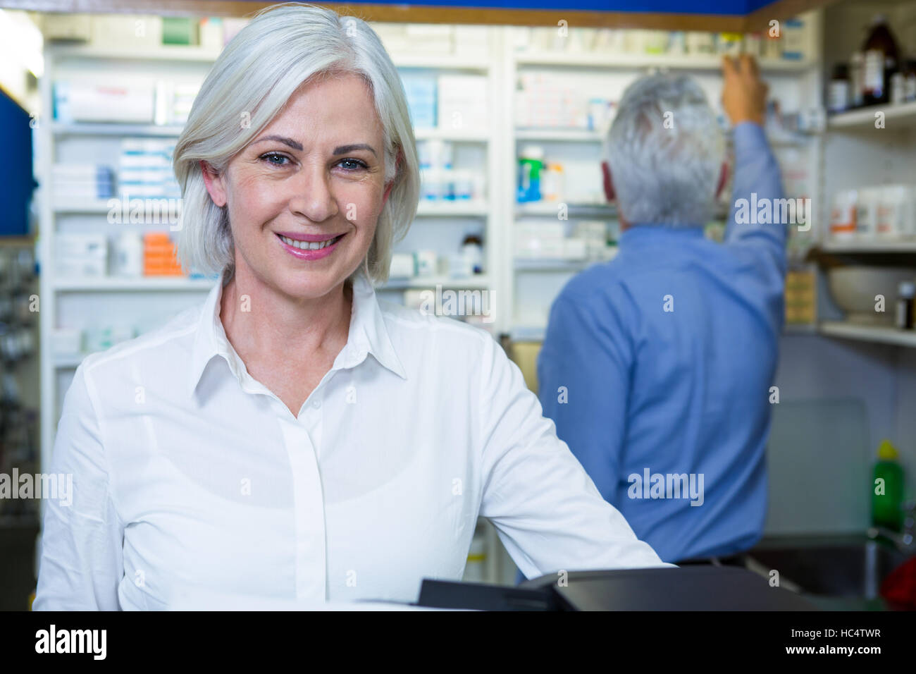 Pharmacist smiling and co-worker checking medicines - Stock Image