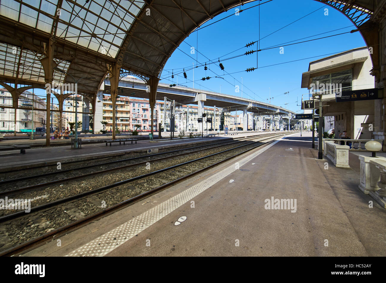 Panorama of the railway station in the center, sunny day, blue sky, a lot of tourists, Rails  under glass a roof - Stock Image