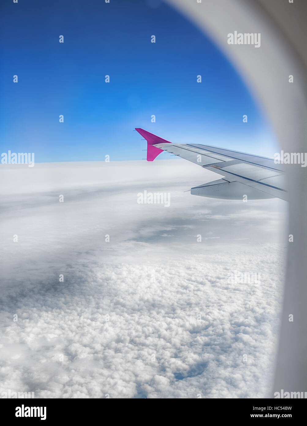 Airplane wing flying above sky and clouds through window aircraft. - Stock Image
