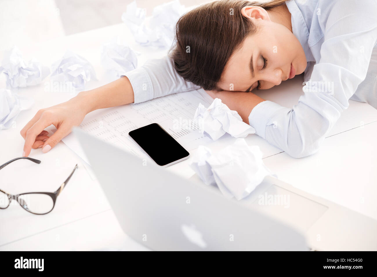 Photo of tired woman at office desk sleeping with eyes closed, sleep deprivation and stressful life concept - Stock Image