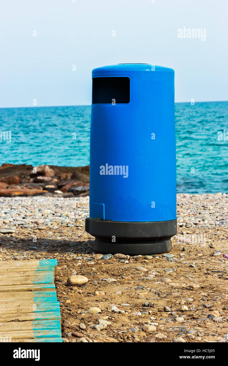 Blue beach trash with walkway. Vertical image. - Stock Image