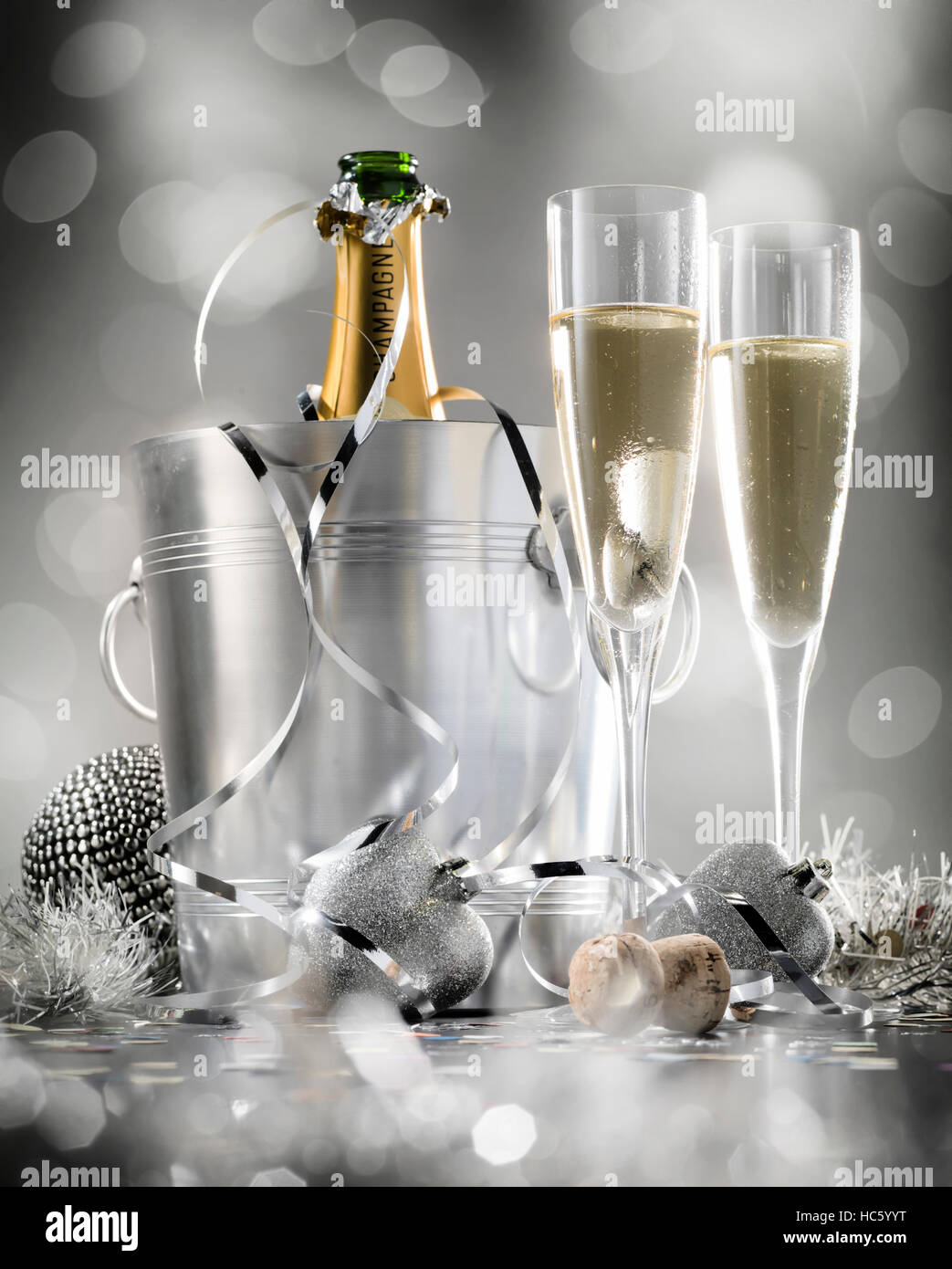 Pair glass of champagne with bottle in metal container. New Year celebration theme with blur spots of bubbles - Stock Image