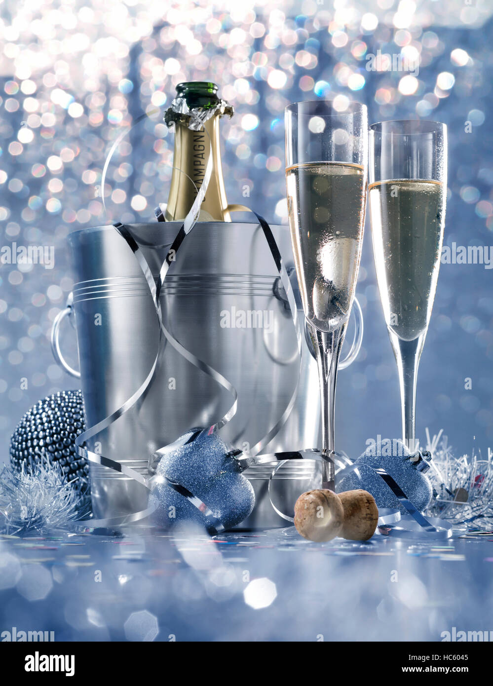 dim light white silver and blue romantic new year eve or christmas table in a luxury restaurant with champagne - Stock Image
