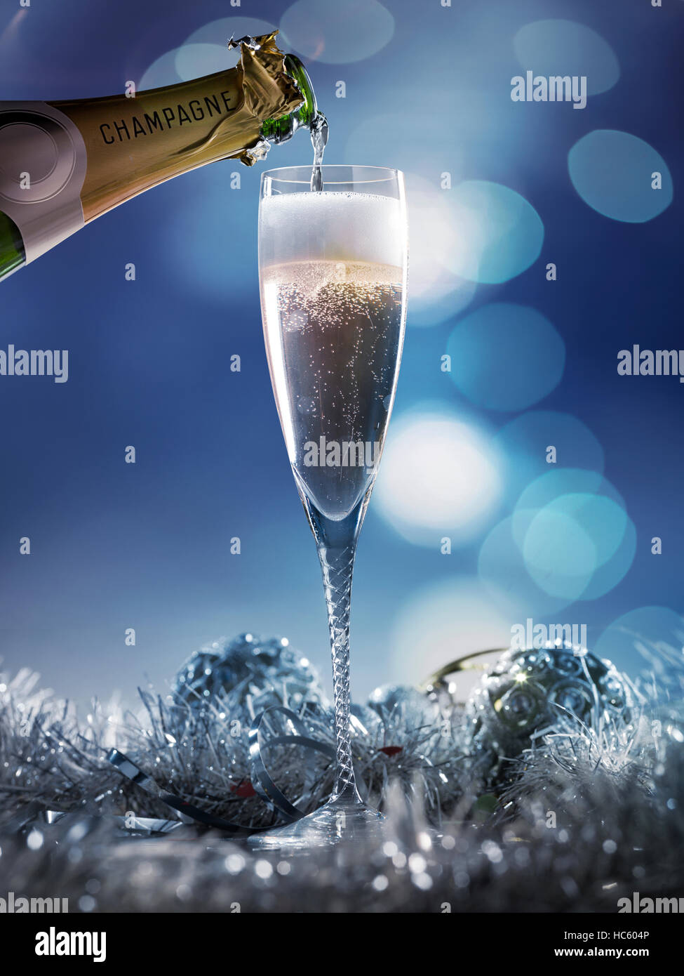 flute of champagne with golden bubbles on dark blue light bokeh background - Stock Image