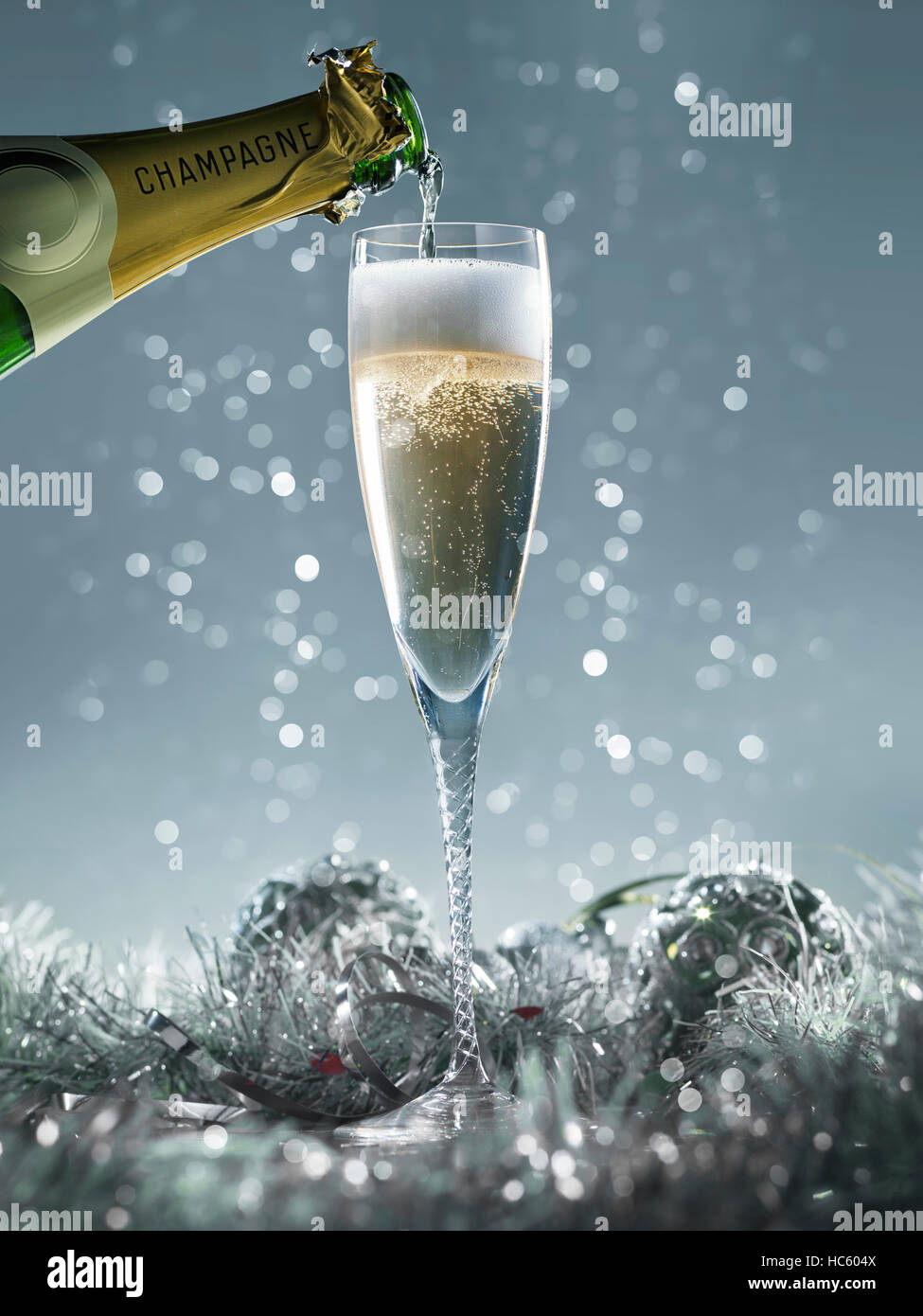 pouring champagne into the glass on a blue christmas background Stock Photo