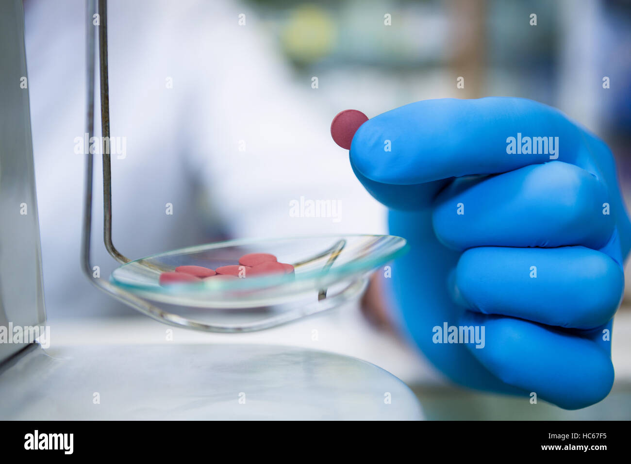 Pharmacist measuring tablets with pharmacy scale - Stock Image
