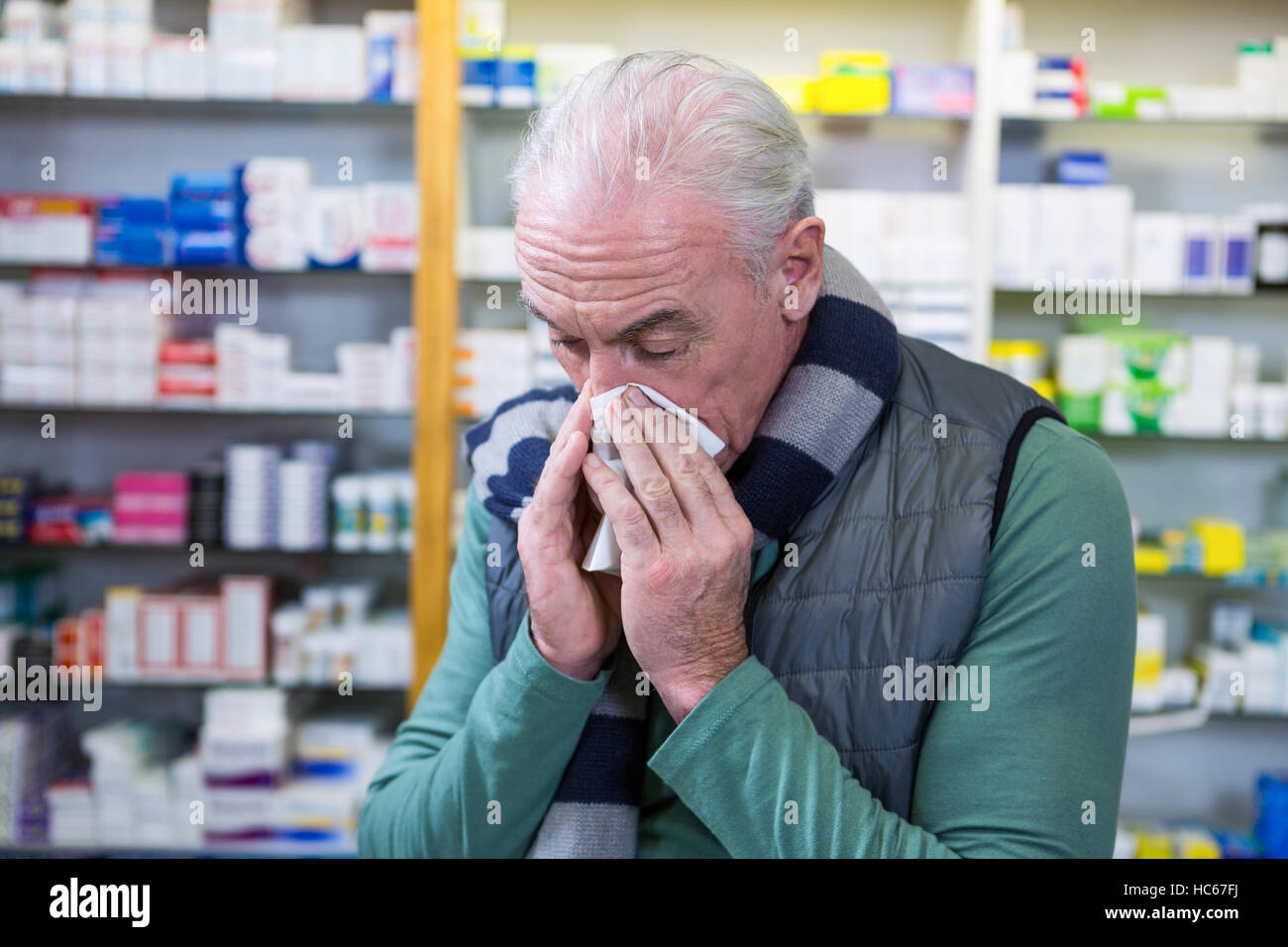 Customer covering his nose with handkerchief while sneezing - Stock Image