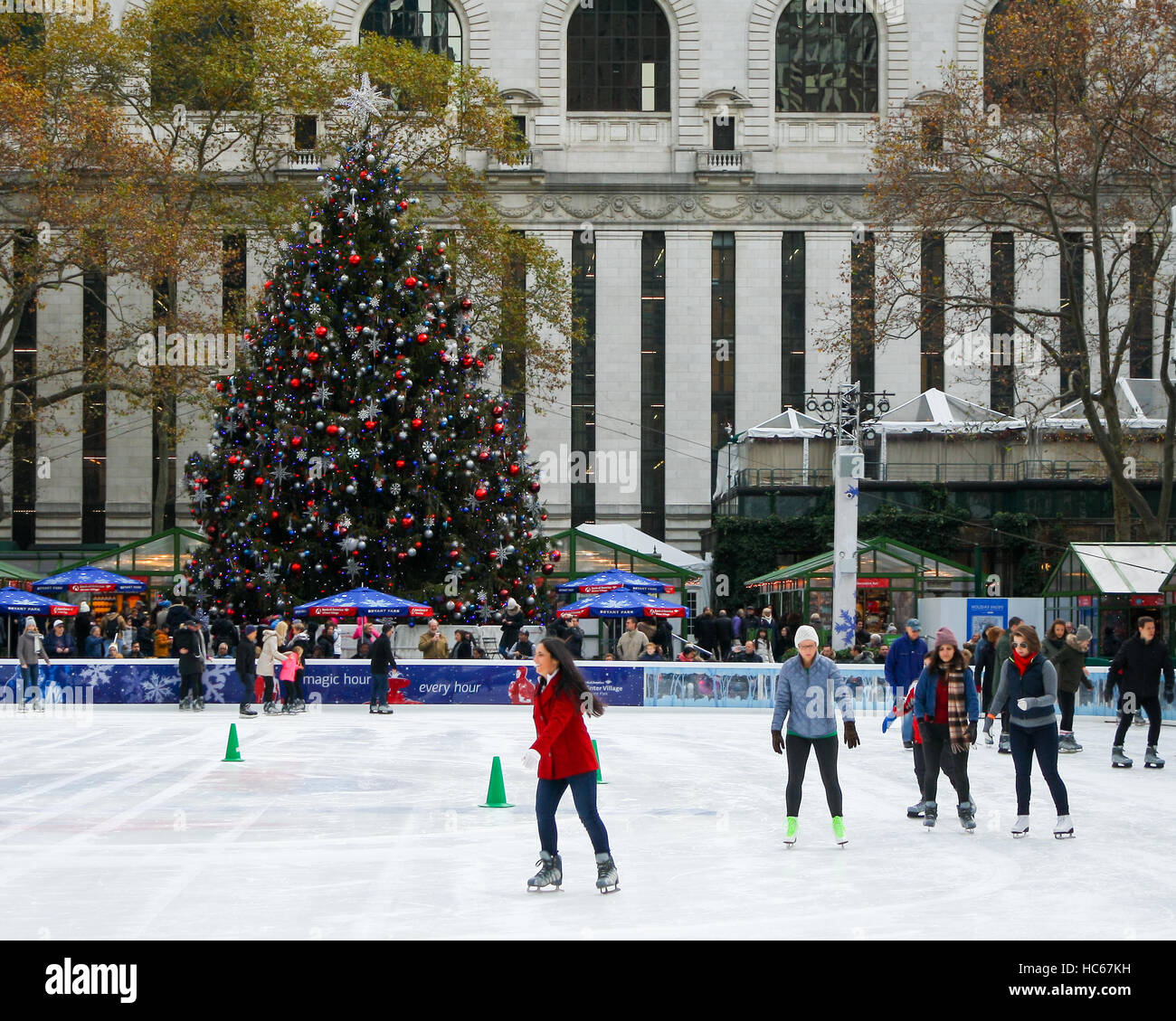 people ice skating in bryant park with christmas tree in background in new york city