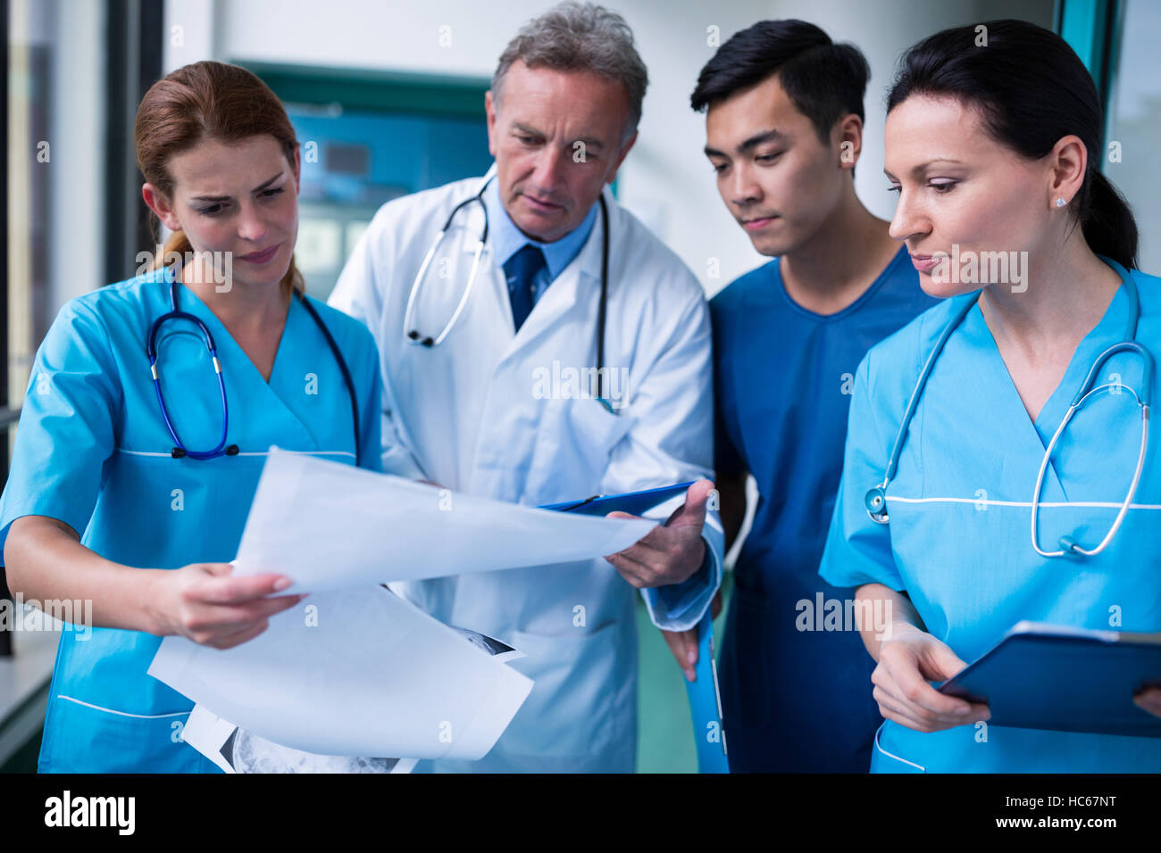 Doctor and surgeons discussing with report in surgical room - Stock Image