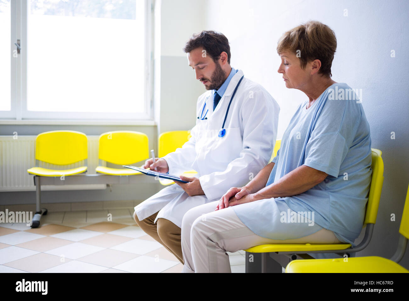 Doctor consulting patient in waiting room - Stock Image