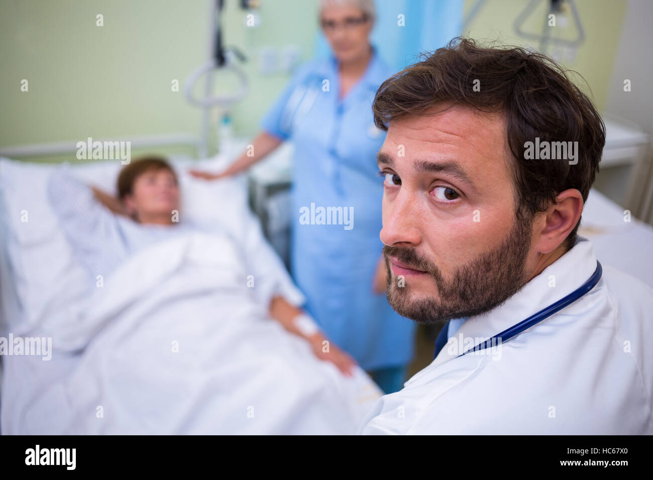 Portrait of doctor standing in hospital room - Stock Image