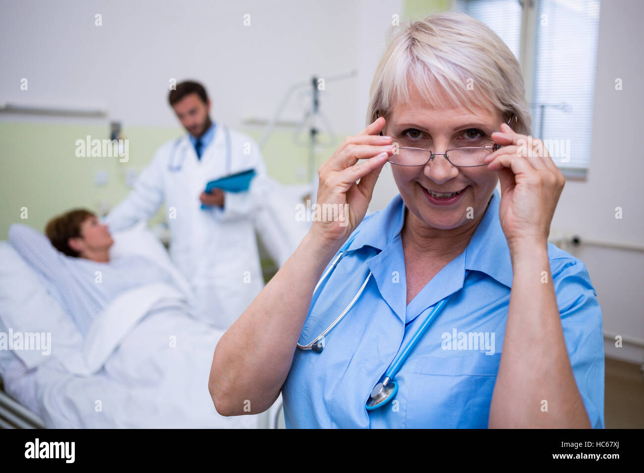 Portrait of smiling nurse wearing spectacle - Stock Image