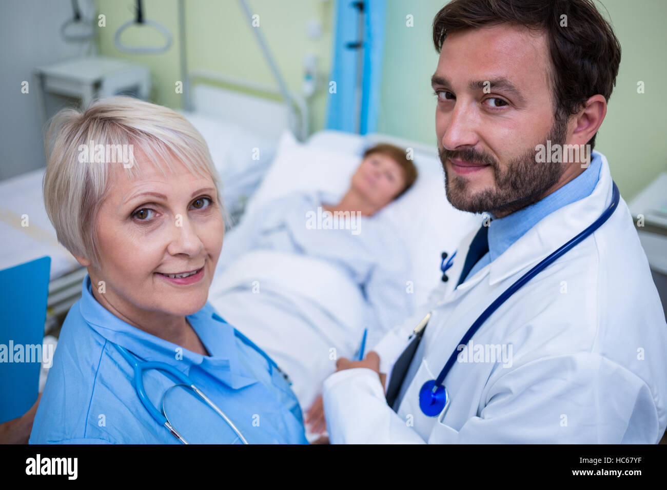 Portrait of doctor and nurse standing in hospital room - Stock Image