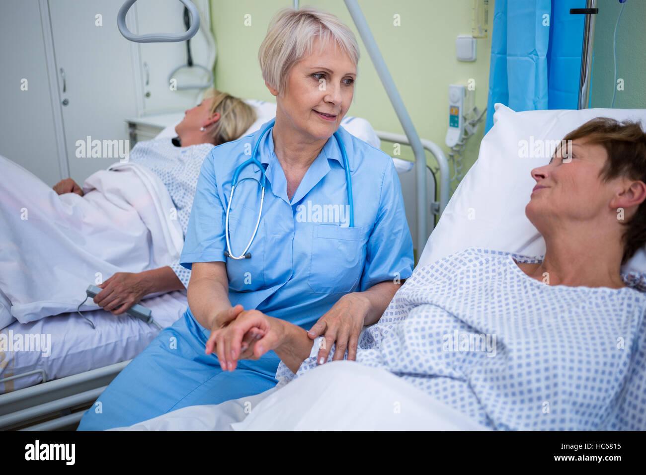 Nurse examining patients pulse - Stock Image