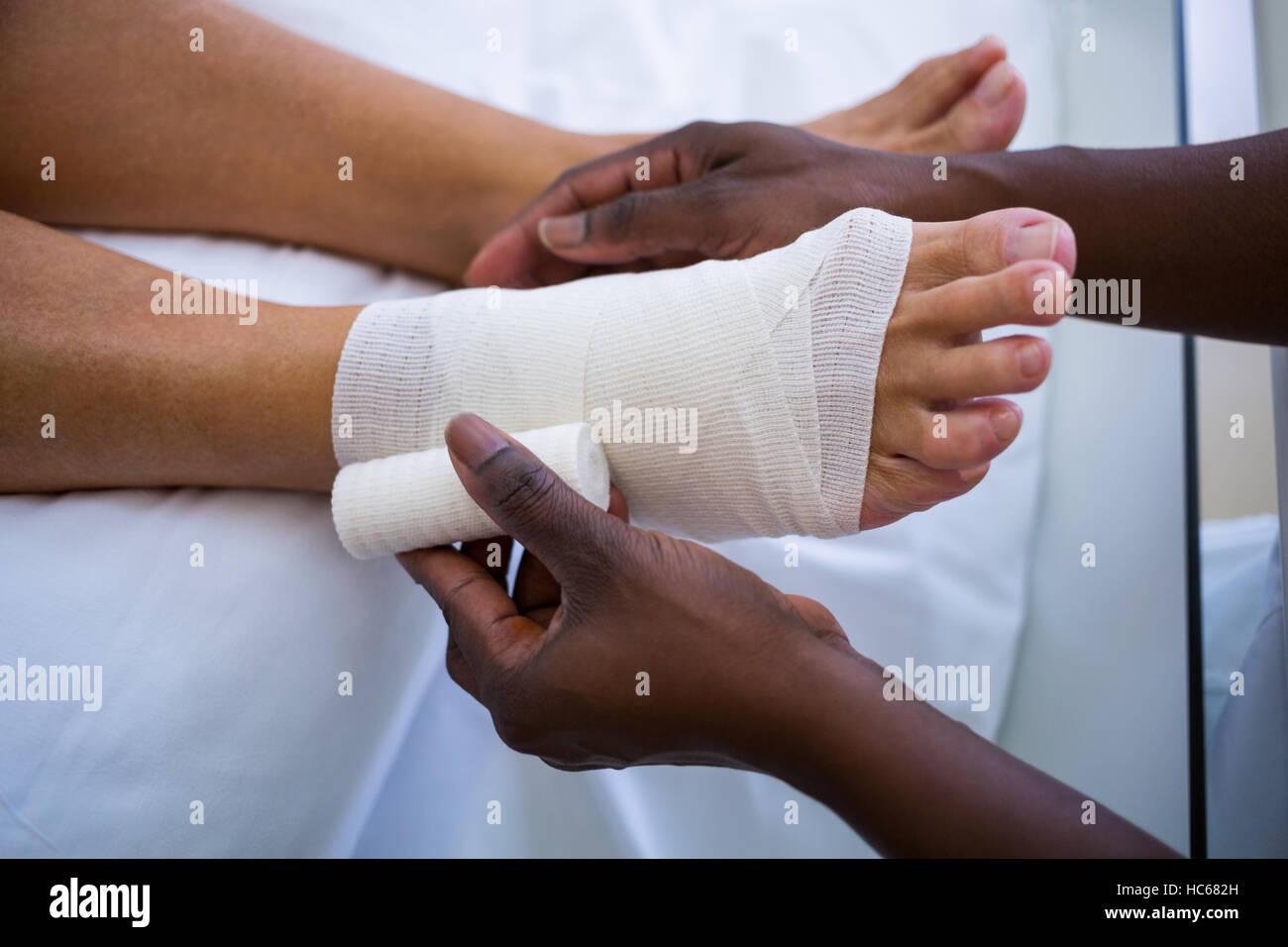 Doctor bandaging patients leg - Stock Image