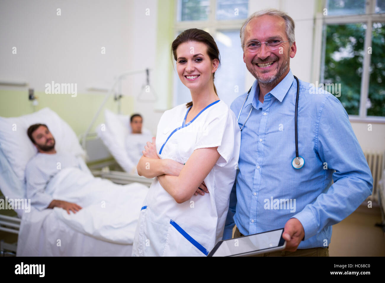 Smiling doctor and nurse standing in ward - Stock Image