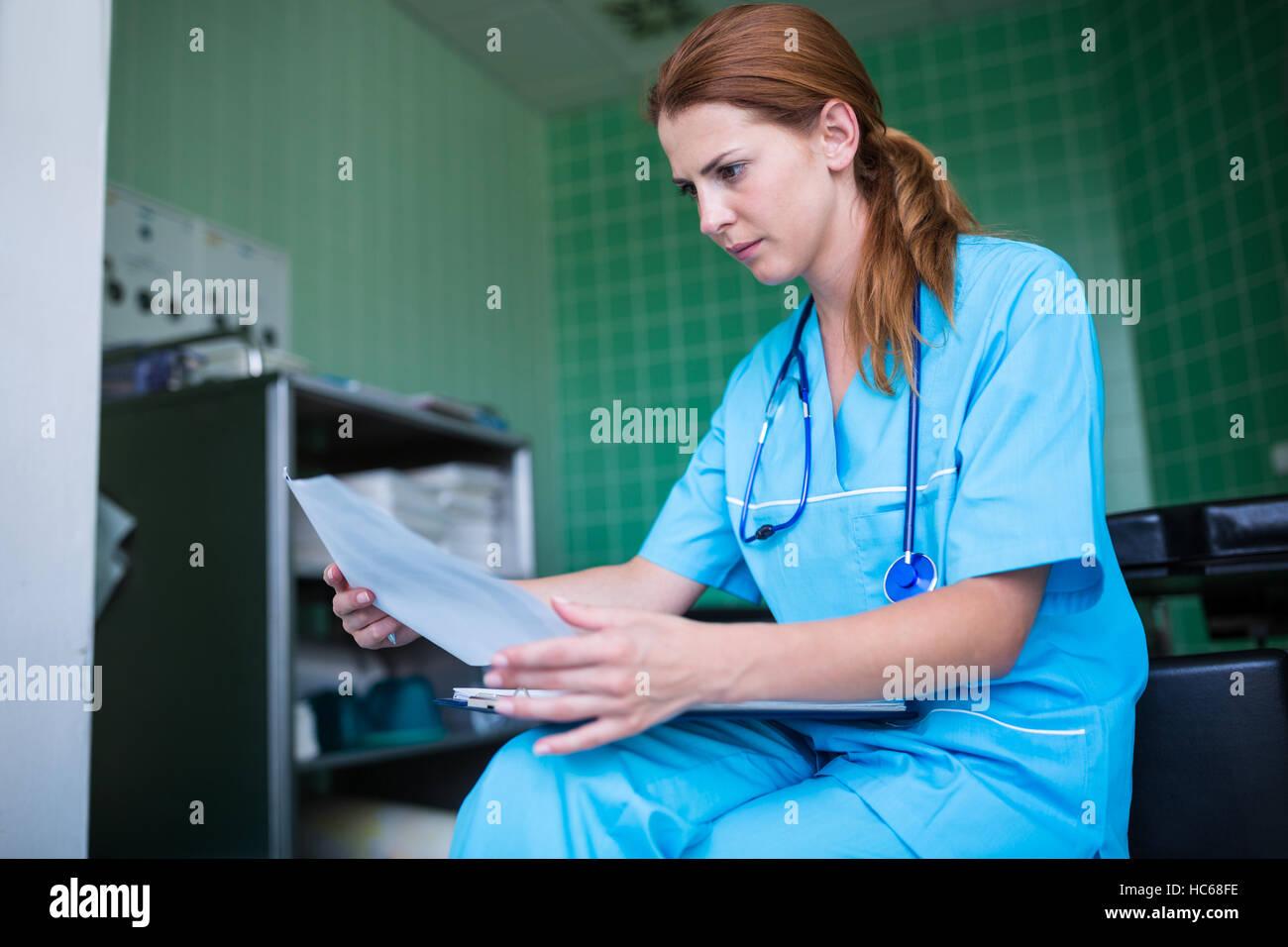 Nurse checking medical report - Stock Image