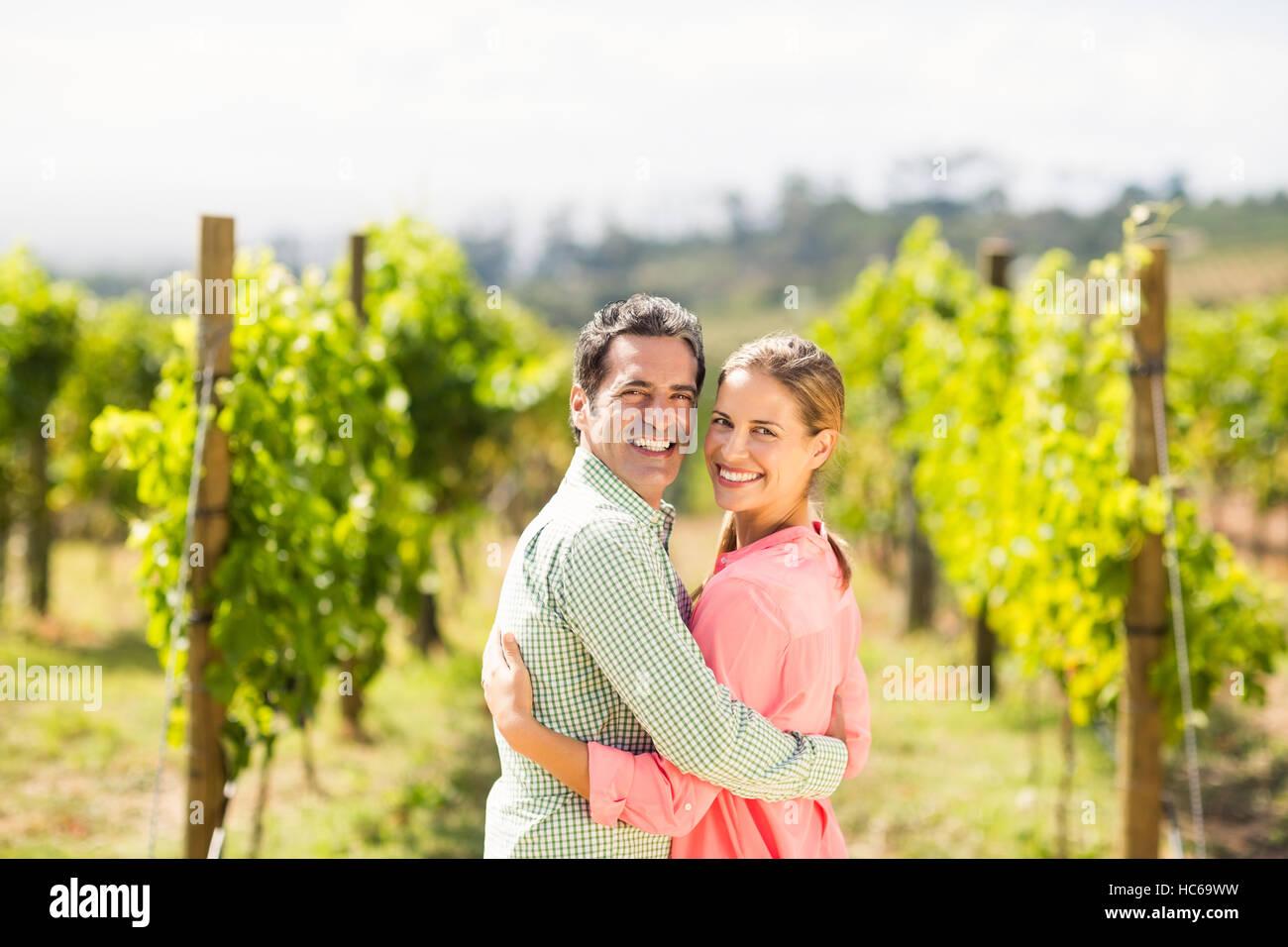 Portrait of happy couple standing with arm around - Stock Image