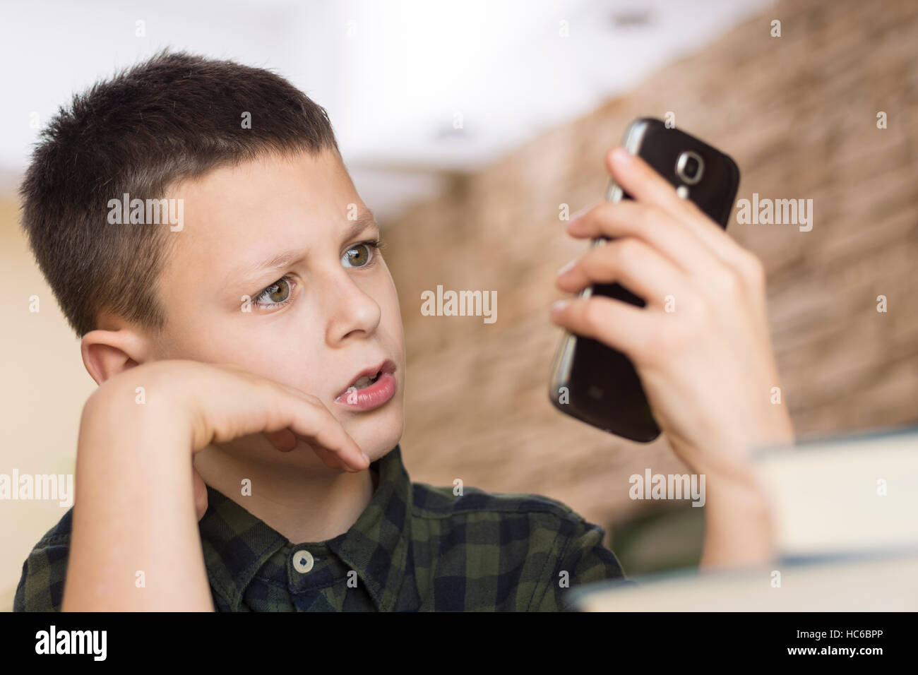 Confused Boy Looking at His Smart Phone. Mobile Phone Talk Concept. - Stock Image