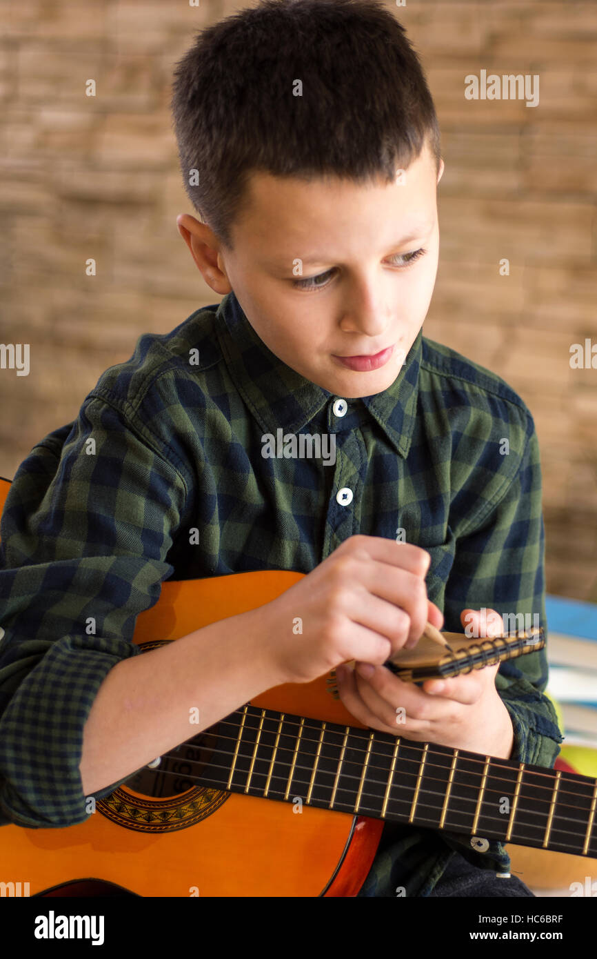 Boy with Acoustic Guitar Writing Songs in Living Room - Stock Image