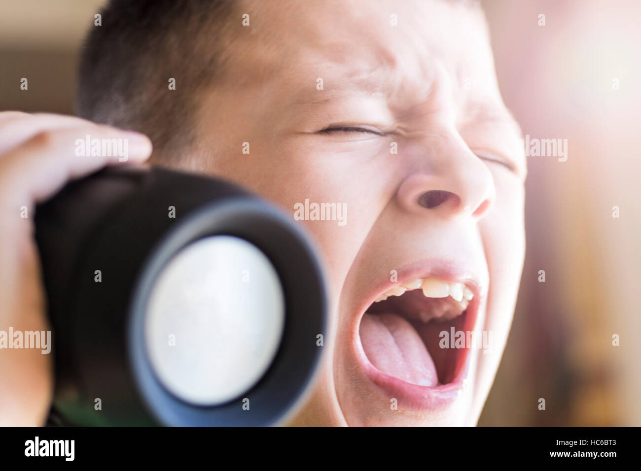 Young Boy Singing Out Loud While Listening Music on Wireless Speaker. Expressive Face. - Stock Image