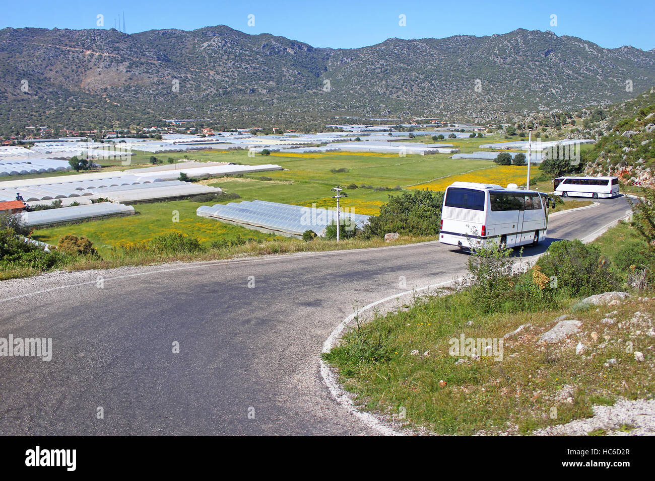 Glasshouses with plastic and touristic buses near village in Turkey - Stock Image